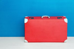 Red retro suitcase at the blue wall. Travel and adventure