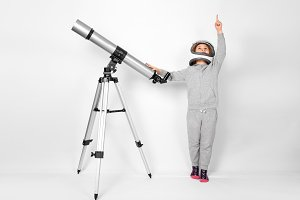 Happy child girl dressed in an astronaut costume standing beside the telescope