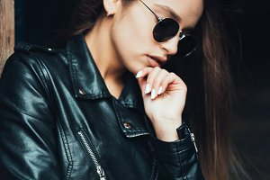 Beautiful girl in a black jacket and sunglasses