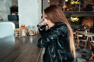 Beautiful girl in a black jacket in a cafe