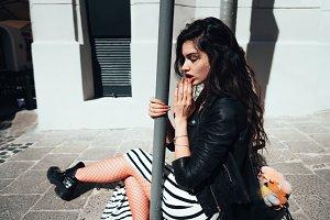 Beautiful fashionable lady sitting on old street