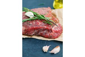 Close-up of raw beef steak on craft paper with garlic and rosemary. Cooking concept. Selective focus.