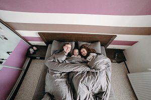 happy child with parents in bed at home