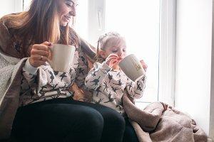 Mom and daughter drink something with mug