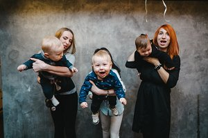 Three moms with their children posing on camera