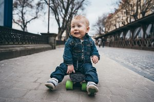 little funny boy with skateboard on the street