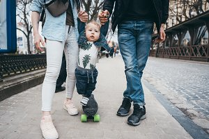 Mom dad and little son together on a walk