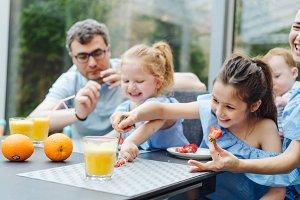 Happy family eating fresh fruit breakfast