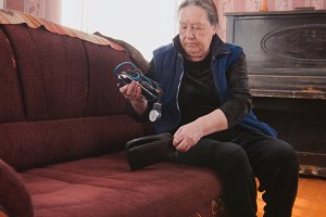 An elderly woman gets out of the case a device for measuring blood pressure