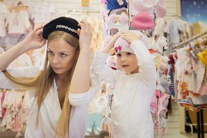Mother and daughter try on cute beanies in front of the mirror