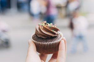 Hand holding homemade cupcake