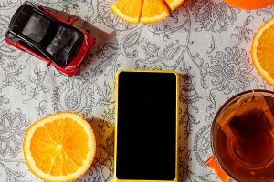 Phone with a black screen. Citrus tea and toy car