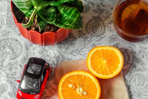 Slices of sliced oranges. Small car. Potted flowers in a pot