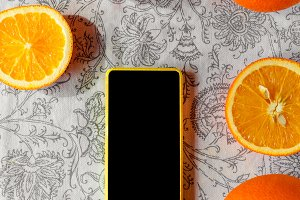 On a tablecloth lie sliced oranges. Yellow phone with black screen