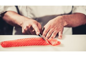 Cook cutting salmon