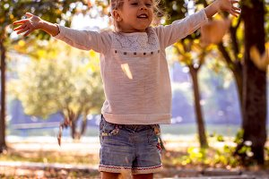 beautiful little girl playing in the Park with autumn leaves