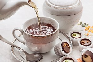 A white cup of tea with a teaspoon and chocolate.