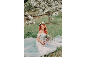 Young woman in a luxurious dress sits on the grass in a blooming garden