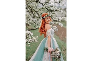 Young woman in a luxurious dress is standing and smiling in a blooming garden