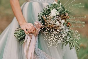 The bride is holding a spring wedding bouquet, close-up