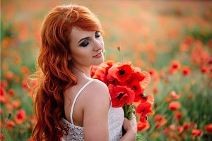 beautiful young red-haired woman in poppy field holding a bouquet of poppies