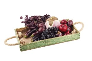 Set of different violet vegetables and fruits in the wooden tray, isolated