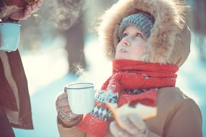 Child drink tea in winter nature