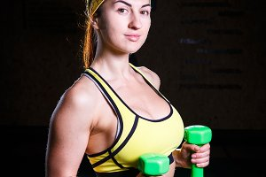 Young beautiful girl in the gym coaches muscles of the hands with green dumbbells. Sports concept