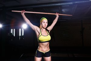 Young beautiful girl is exercising in the gym. Holds a stick over his head for trinorvki muscles of legs . Sports concept