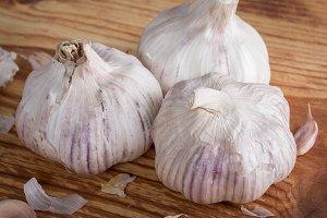 Three garlics on wooden table