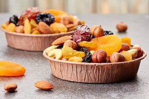 Paper forms with mix of dried fruits and nuts over stone background