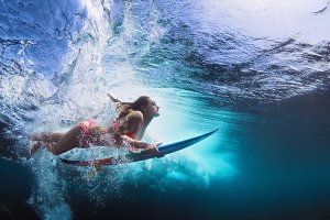 Surfer girl dive under wave