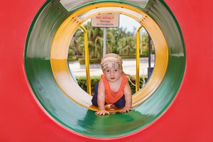 Child crawling in playground tube