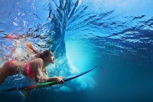 Surfer girl diving under wave