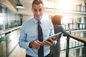 Cheerful businessman with tablet looking at camera