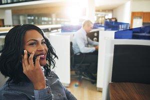 Pretty black female employee talking smartphone at workplace