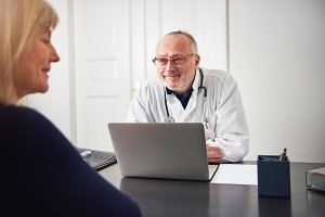 Smiling adult doctor listening patient at laptop