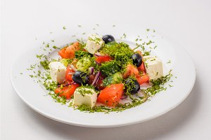Greek salad in a plate on a white background
