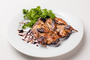 quail roasted in a dish on a white background