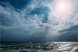 Blue sea with waves and clouds in the sky