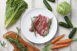 Raw duck breast in white plate and vegetables