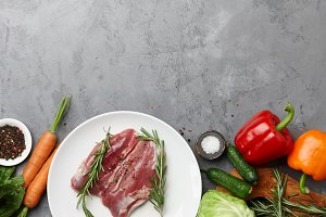 Raw duck breast in white plate with vegetables