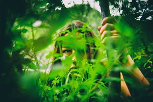 Woman looks through green leaves