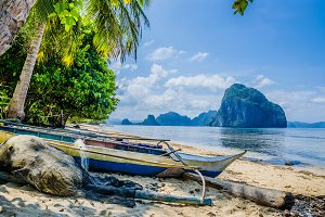 Fishing boat and net on shore under palms.Tropical island landscape. El- Nido, Palawan, Philippines