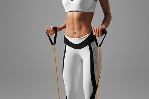 fitness woman doing training exercises for hands and back with expander