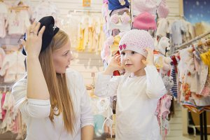Mother and daughter trying on beautiful hats