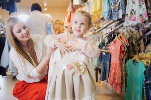 Little girl holding in the hands a beige summer dress
