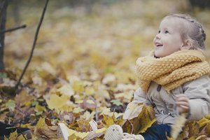 Portrait of little happy cute girl plays in autumn park among yellow leaves