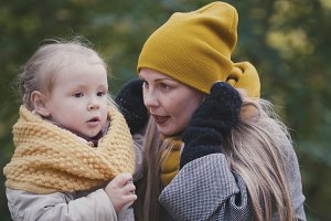 Baby blonde child girl with her mommy plays in autumn park, close up