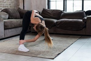 Sporty young female doing stretching exercise bending forward during home workout